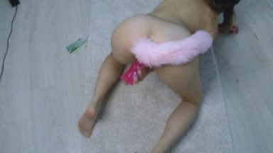 sexy kitty with a tail in the ass fucks herself in the pussy on the carpet